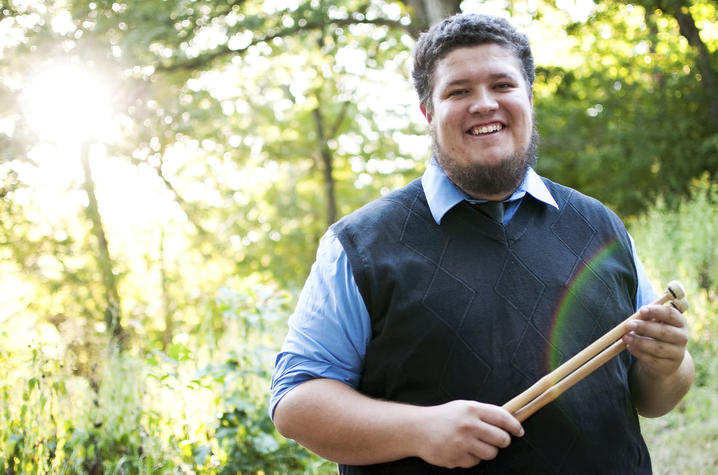 photo of Tyler Swick holding drumsticks outside