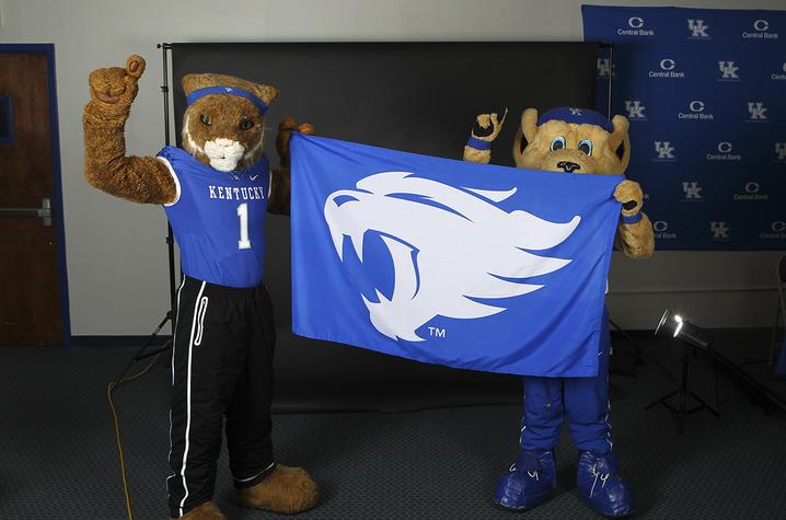 photo of UK mascots holding flag with UK Wildcat photo on it