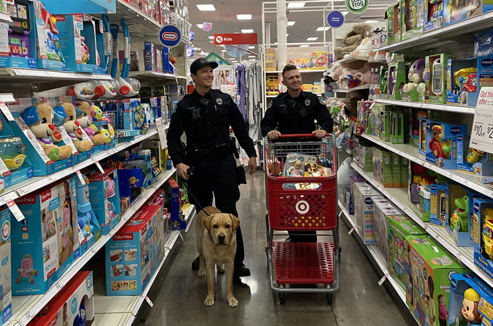 photo of two UK Police officers and the therapy dog in a toy aisle shopping for the Cram the Cruiser toy drive inn 2019