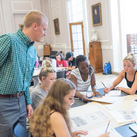 photo of Matthew Strandmark working with students in King Library