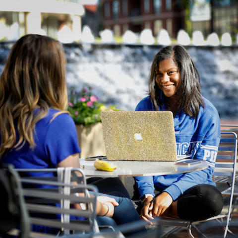 Photo of students with a laptop
