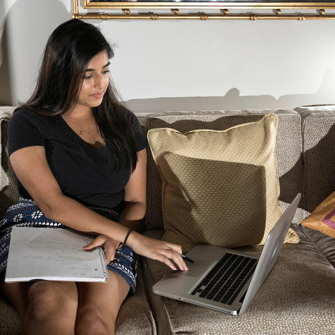 photo of student studying with laptop and notepad on couch