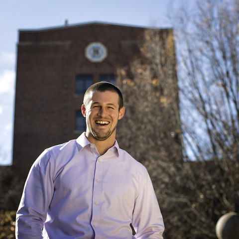 Alex Elswick smiling while standing in front of the Funkhouser building