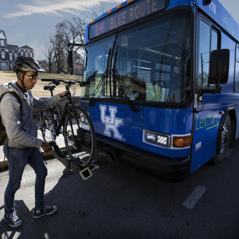 photo of man adding bike to bus