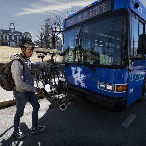Photo of person loading bike onto transit bus