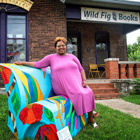 photo of Crystal Wilkinson seated on her book's bench outside Wild Fig