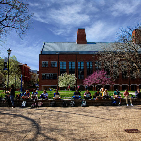 Photo of students sitting outside of Whitehall Classroom Building.