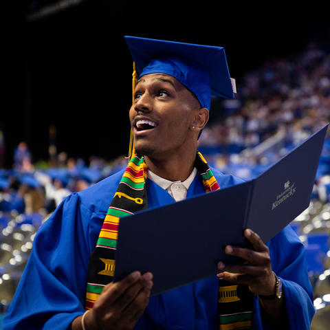 Male graduate in cap and gown holding diploma