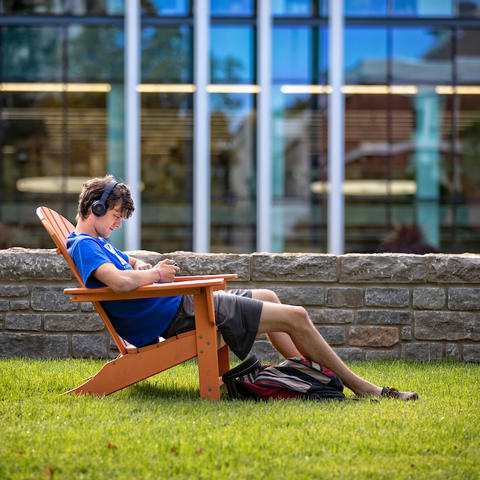 male student with headphones on sitting in an outdoor chair