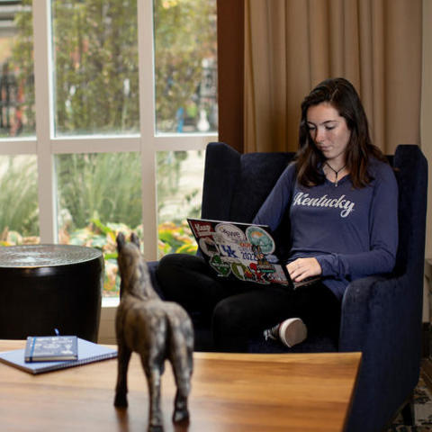 photo of student in recliner on laptop