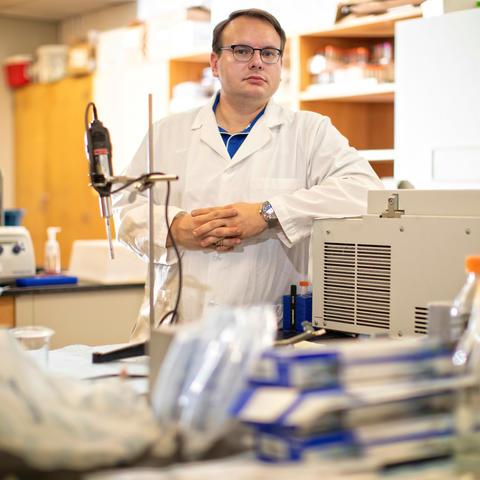 Stuart Lichtenberg in lab coat behind lab table
