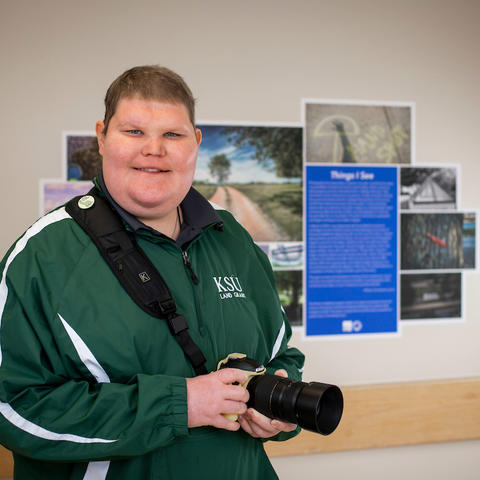 Photo of Chris Lyons with camera in front of gallery