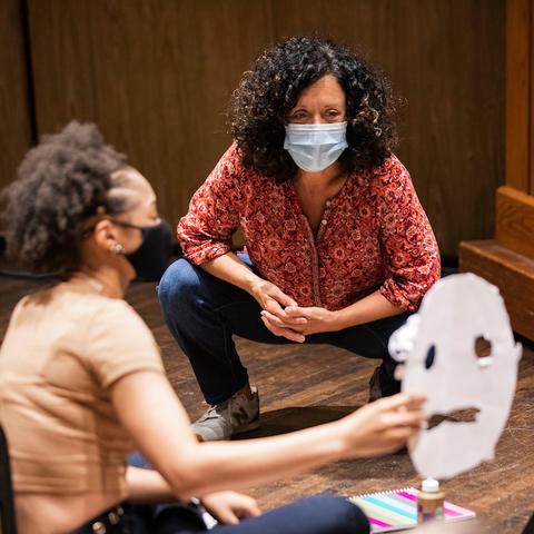 photo of Nancy Jones looking at students Greek mask in theatre class