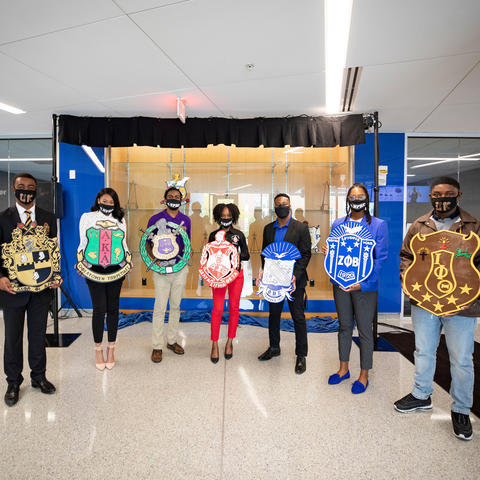 NPHC fraternity and sorority members hold crests