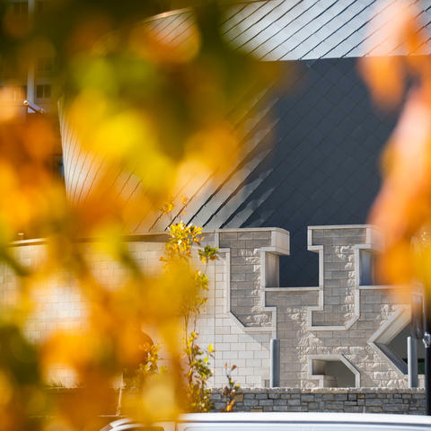 """The large """"UK"""" in front of the Gatton Student Center framed by fall foliage"""