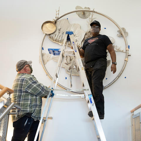 "photo of Garry Bibbs on ladder installing ""Being Aliver"" at Lexington Senior Center"