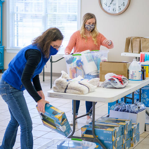 Wolfe County extension agents, Heather Graham, foreground, and Alyssa Cox, sort through donations at the Wolfe County Extension office