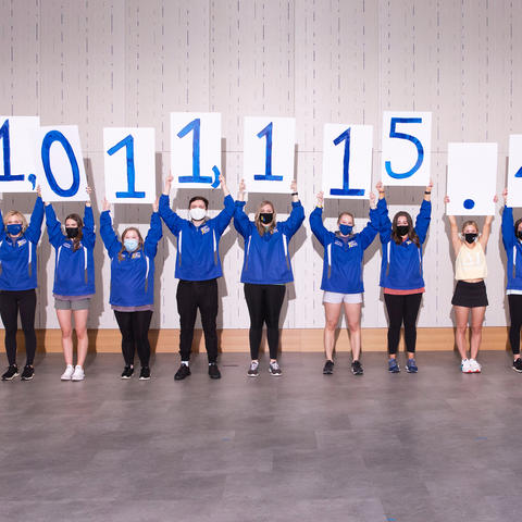 Photo of students holding up signs revealing the DanceBlue fundraising total of $1,011,115.49.