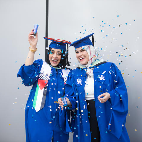 Two UK graduates in caps and gowns with confetti