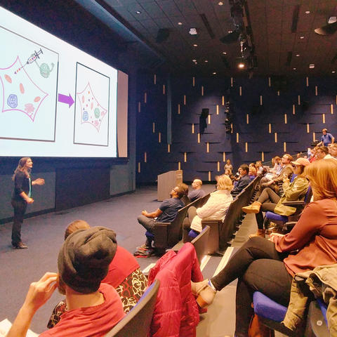 photo of student researcher presenting to audience in Worsham Cinema