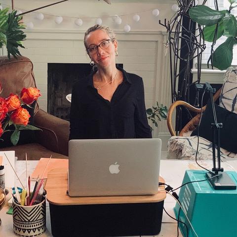 photo of Aubrey Nibert seated in her studio with laptop to teach GSA visual art online