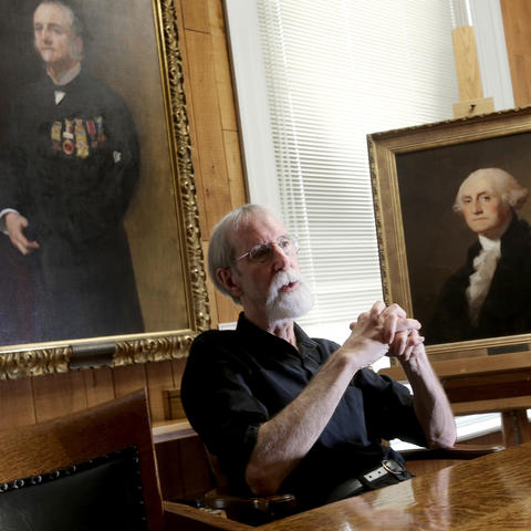 photo of Barry Bauman seated in front of portraits of Lucius Fairchild and George Washington by artists by John Singer Sargent and Thomas Sully