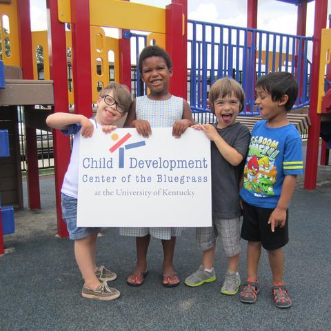 photo of kids holding Child Development Center of the Bluegrass sign