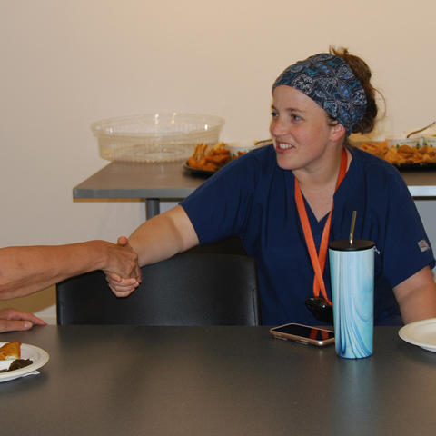 Dr. Callie Dowdy, surgical resident, greets one of the artists at the ArtsCAFE open house.