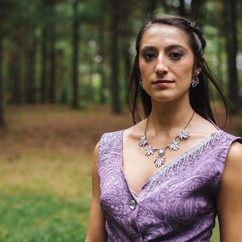A woman with dark hair and a purple dress stands in the foreground with a forest behind her