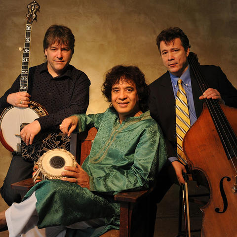 photo of Bela Fleck, Zakir Hussain (seated) and Edgar Meyer with instruments