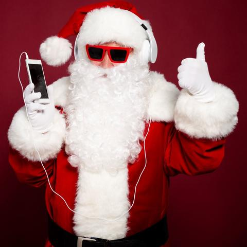 stock photo of Santa in sunglasses listening to an ipod giving a thumbs up