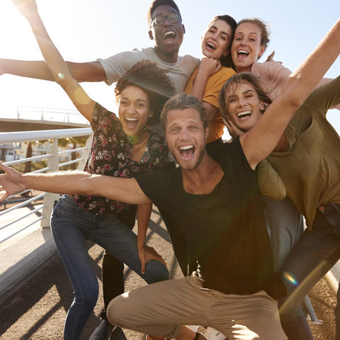 Six diverse young adults with big smiles and outstretched arms are huddled for a group photo. They are outside on a sunny day and appear to be standing on a pedestrian bridge.