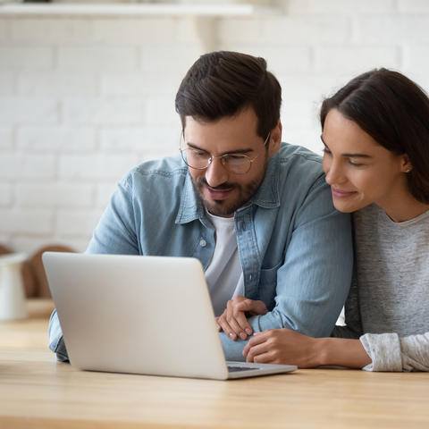 Couple seated at wooden table looking at laptop