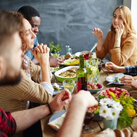 photo of young people around table with food