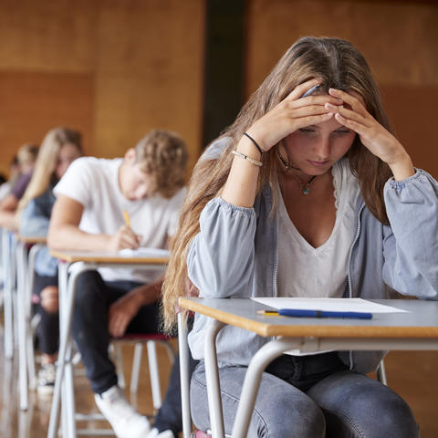 stock photo of female student with head down staring at page on desk