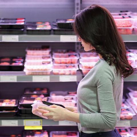 Woman holding meat package in grocery store