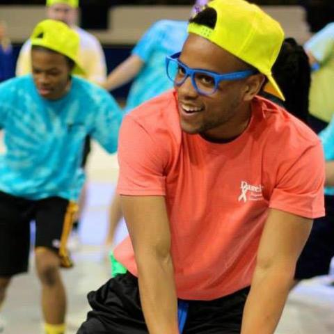 Jordan wearing a neon yellow hat and bright orange shirt dancing