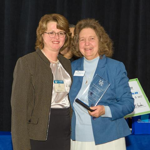 Kim Henken, left, presents award to Judy Hetterman