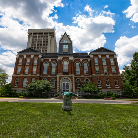 photo of UK's Main Building with puffy clouds in the blue sky