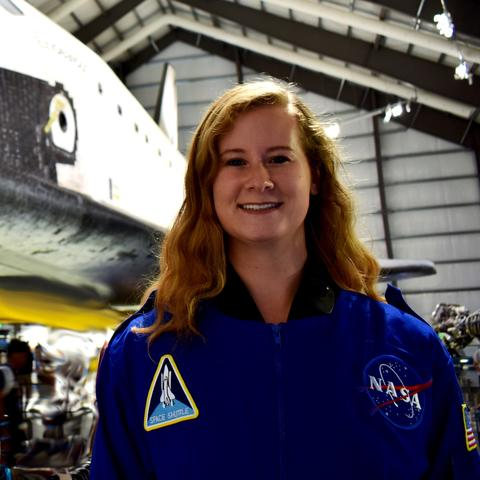 headshot photo of Esther Putman in NASA jumpsuit in front of shuttle