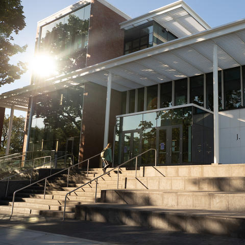 photo of front of the Rosenberg College of Law Building and a student walking up the steps
