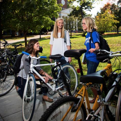 Girls talking by a bike rack.