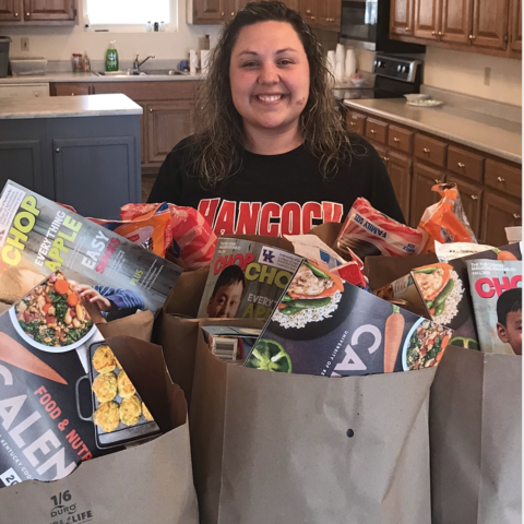 Bethony Morris standing with bags of food
