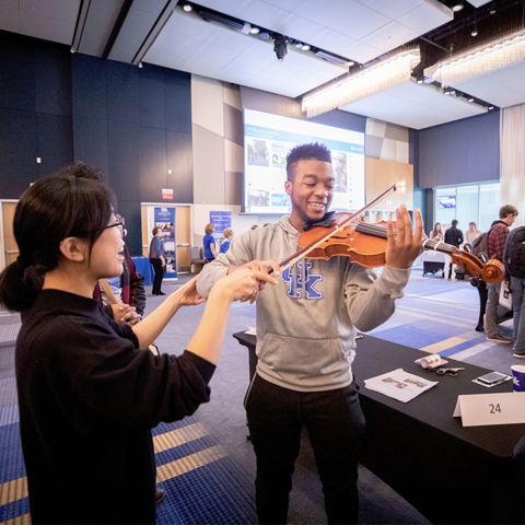 Student holding violin (right) with assistance from expert (left)
