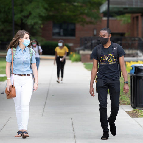 photo of students in masks walking on campus