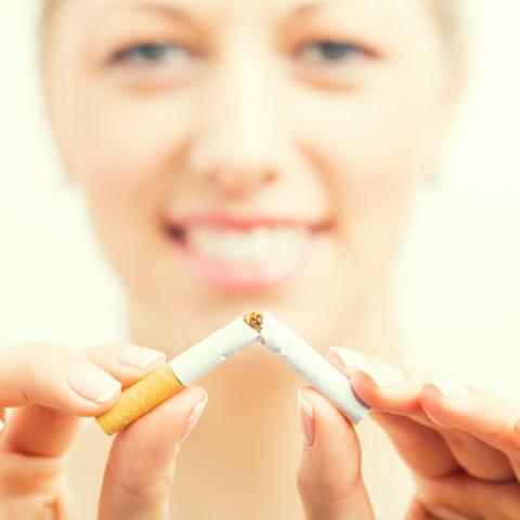 Woman breaking cigarette in half