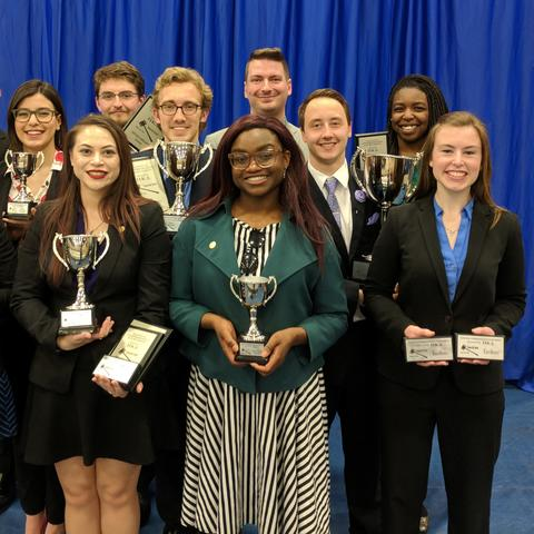 Photo of UK Speech and Debate Team posing with trophies.