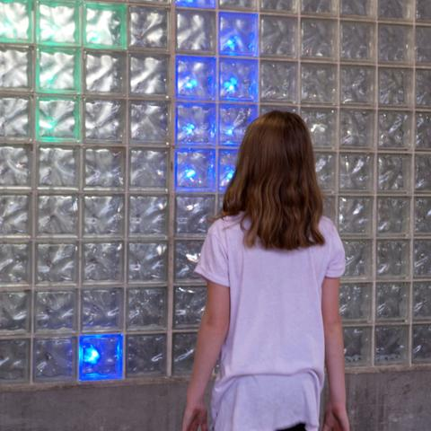 photo of child interacting with LED installation created by UK College of Design