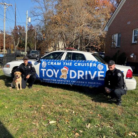 "Photo of Officer Michael Culver, K-9 Hudson and Officer Ryan Johnson in front of the cruiser with a banner that says ""Cram the Cruiser"" toy drive."