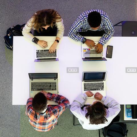 People sitting, working on laptops